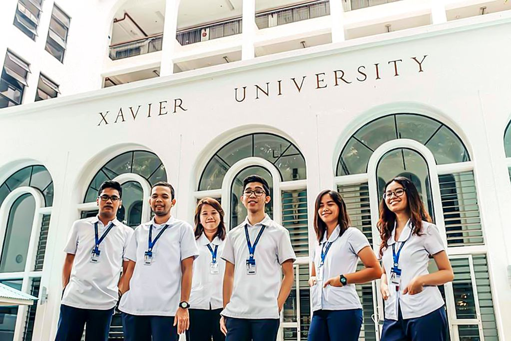 """A group of six students stand outside wearing matching white shirts in front of a white building that is labeled """"Xavier University"""""""
