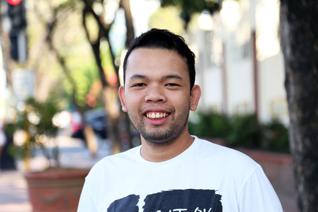 A young man standing outside on a street smiles, wearing a white T-shirt.
