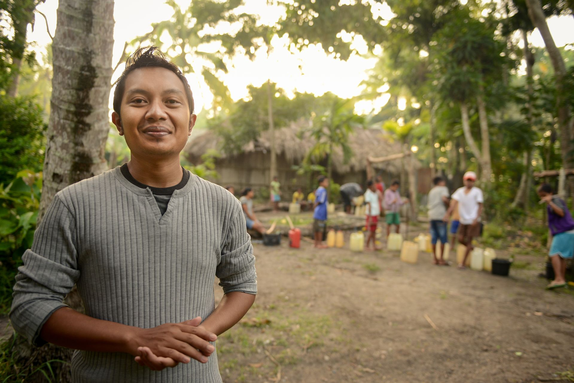 A man in a gray shirt stands outside in front of palm trees and a grass thatched building at sunset with people in a line in the background gathering water