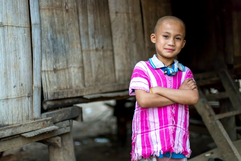 A portrait of a male child, boy, Aekreetoo who is wearing his pink Karen traditional shirt as his prized possession. He is standing inside of his house.