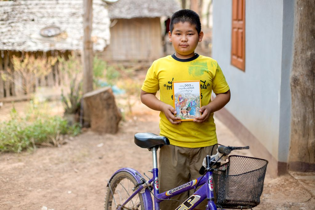 A portrait of a boy, male child, Phithawat wearing a yellow shirt is holding a Bible and standing behind his purple bicycle, bike.