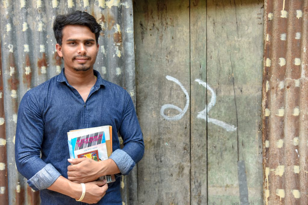 An adolescent male, teenager, Sujon wearing a blue denim shirt is holding several of his books. He is standing in front of a corrugated metal wall, building and a wooden doorway.