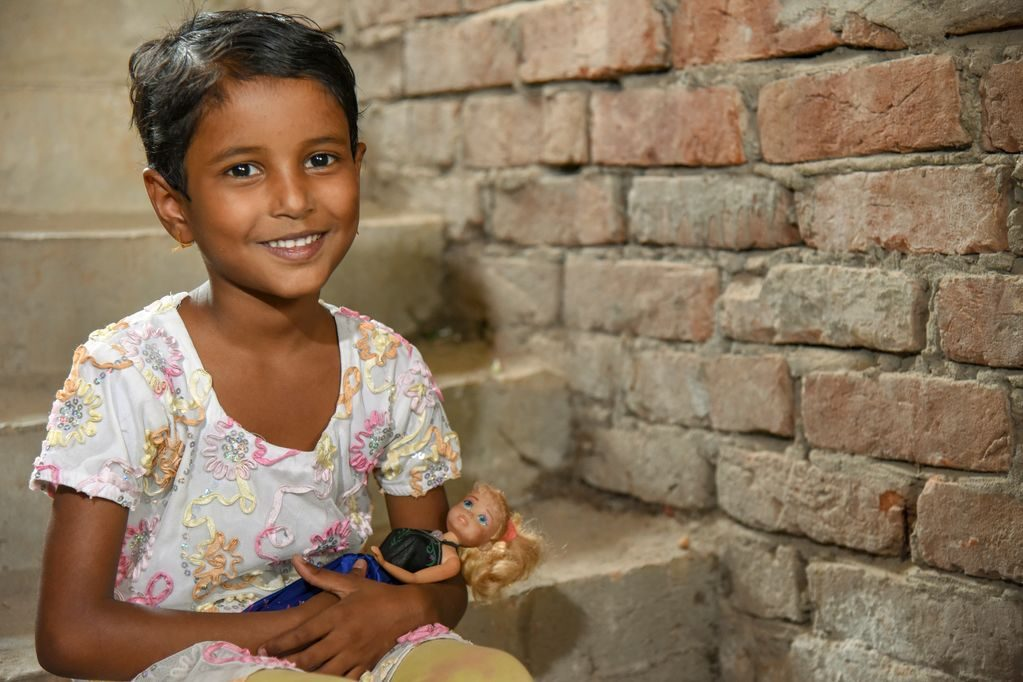 Portrait of a little girl, female child, Ramina beautifully smiling with her doll on the stairways to her brick apartment home.