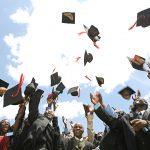 Graduates in Uganda wearing robes throw their graduation caps in the air.