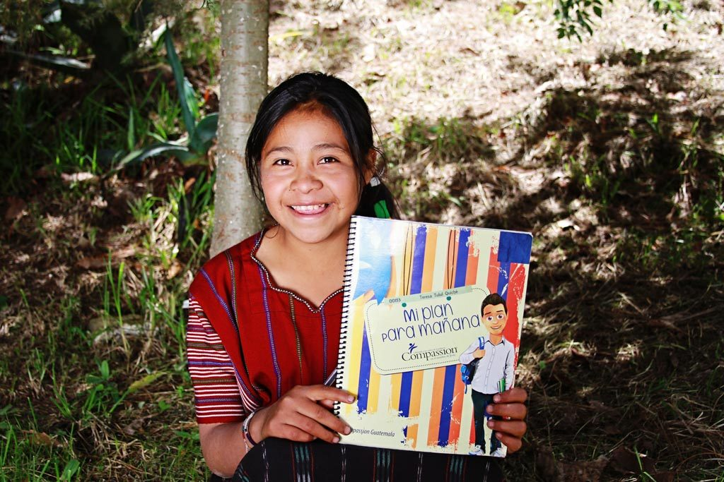 """A girl in Guatemala proudly displays her """"My Plan for Tomorrow"""" workbook."""