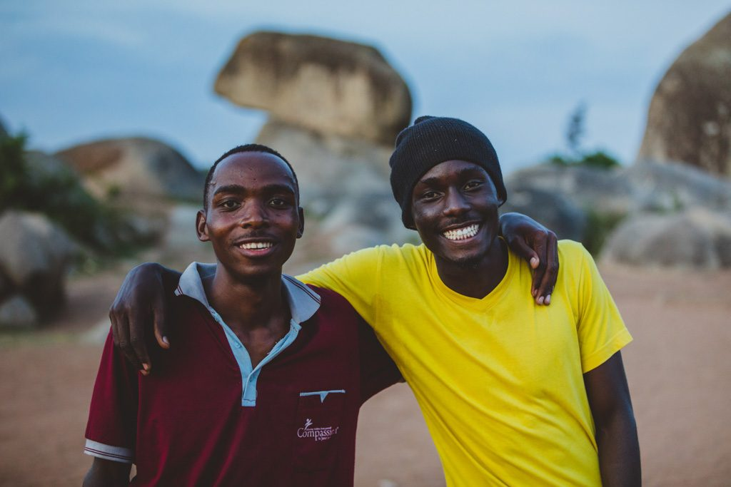 Twin brothers stand together with their arms around eachother's shoulders and smile.