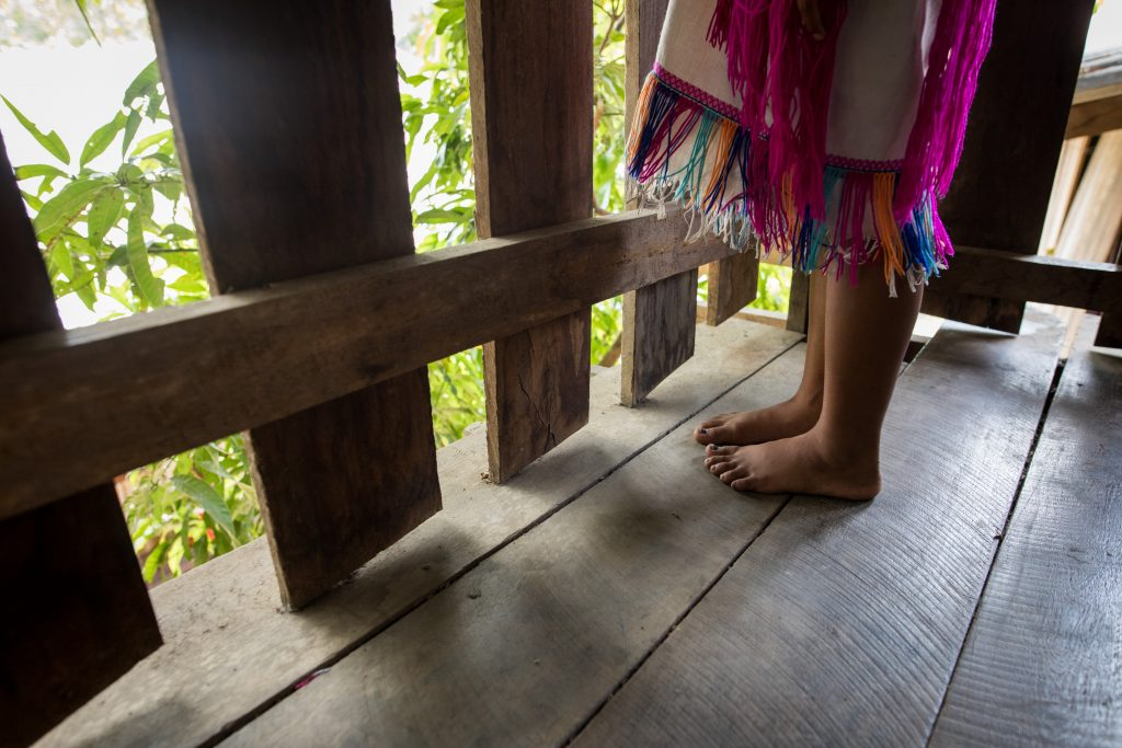 A girl in a traditional Karen dress stands on a wooden floor with a wooden fence in front of her. Pictured is only her feet.