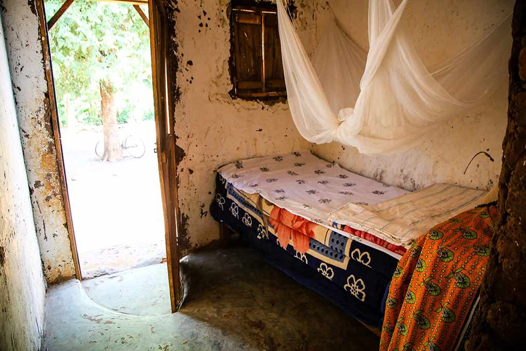 A small room with a bed in the corner, covered by a mosquito net.