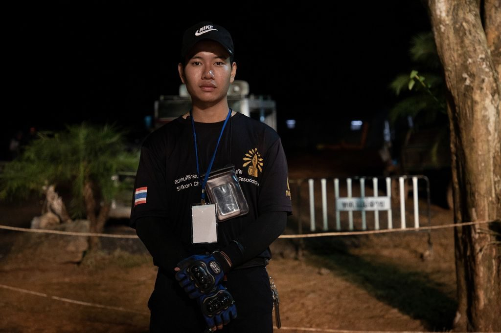 A young man in black wearing a badge and a black hat stands outside in the dark.