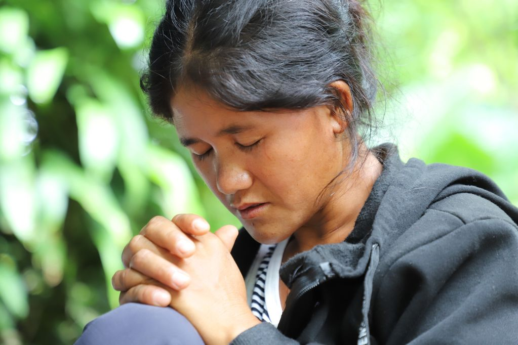 A woman in a black coat clasps her hands while closing her eyes and praying.