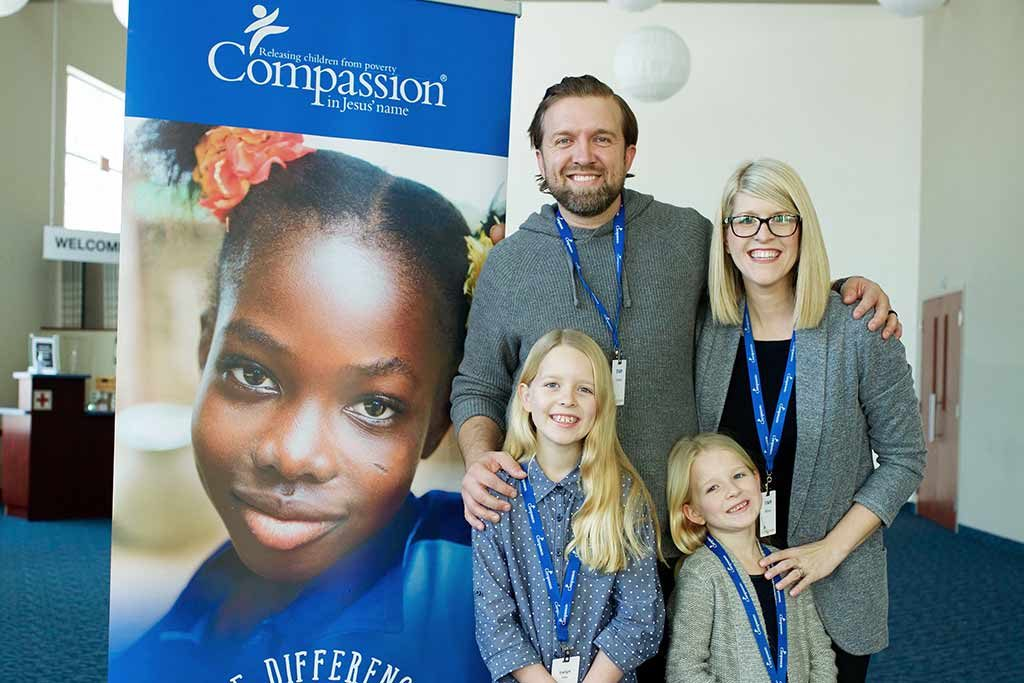 A smiling family of four stands in front of a poster that says Compassion.