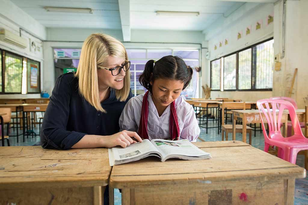 A blonde woman sits at a table in a classroom with a girl in w white shirt, reading a book together