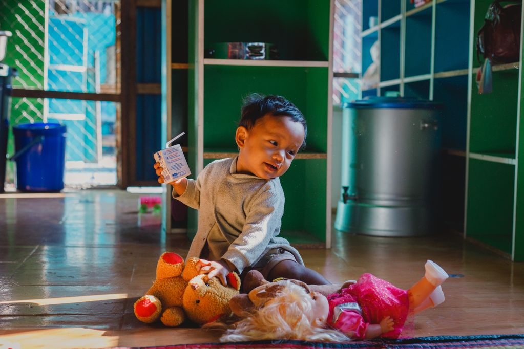 Patanree sits on the floor with her toys, drinking a juice box and smiling.