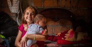 A woman from Ecuador holds her baby close to here chest and smiles happily in our direction.