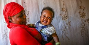 A Ugandan women wearing a red shirt and head dress smiles at the baby she holds in her arms.