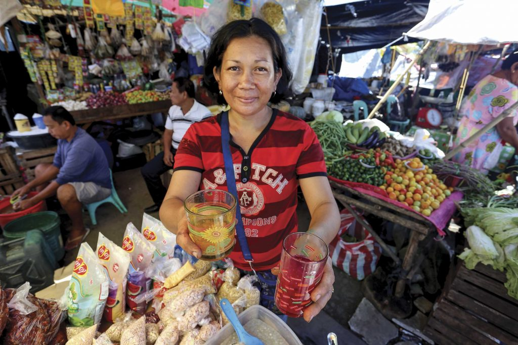 An adult woman, vendor, Narcissa Rubis, the mother of Neriel Rubis, wearing a striped red shirt, holds out glasses of red and yellow bright colored tapioca, snacks, food, she is selling at her open market, booth, tables, stall, store, shop, with trays of fresh vegetables, and food on the tables all around her in the covered market.
