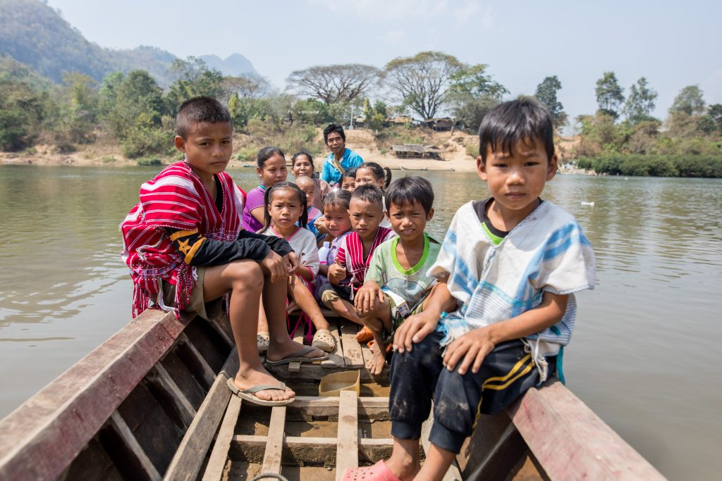 Multiple children are pictured in a boat along the Moei River.