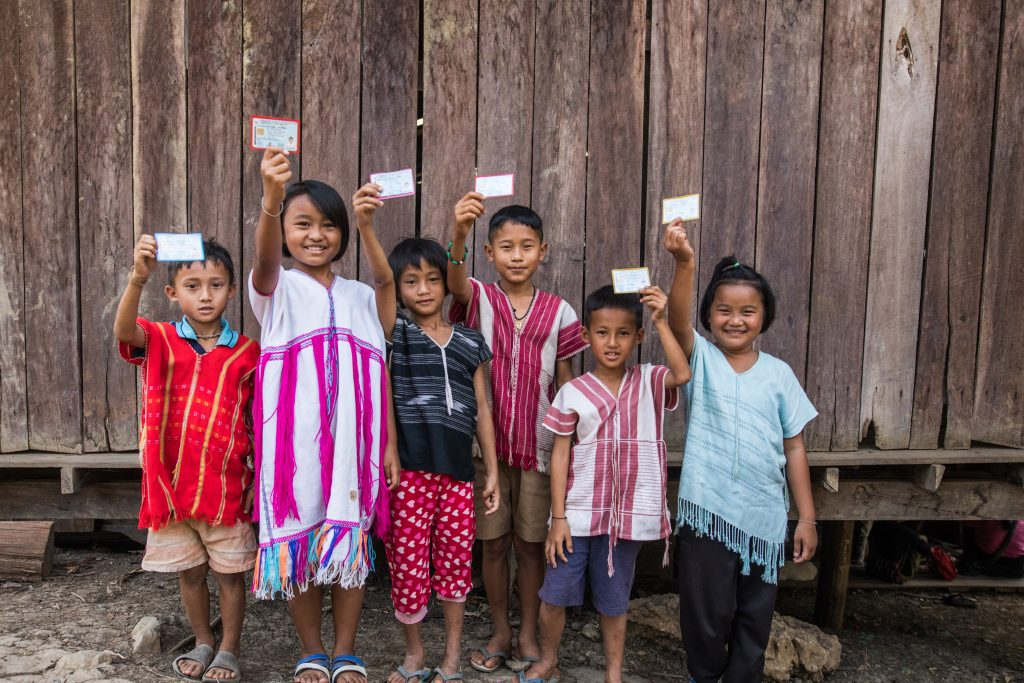 Six children smiling against a fence holding their Thai citizen cards.
