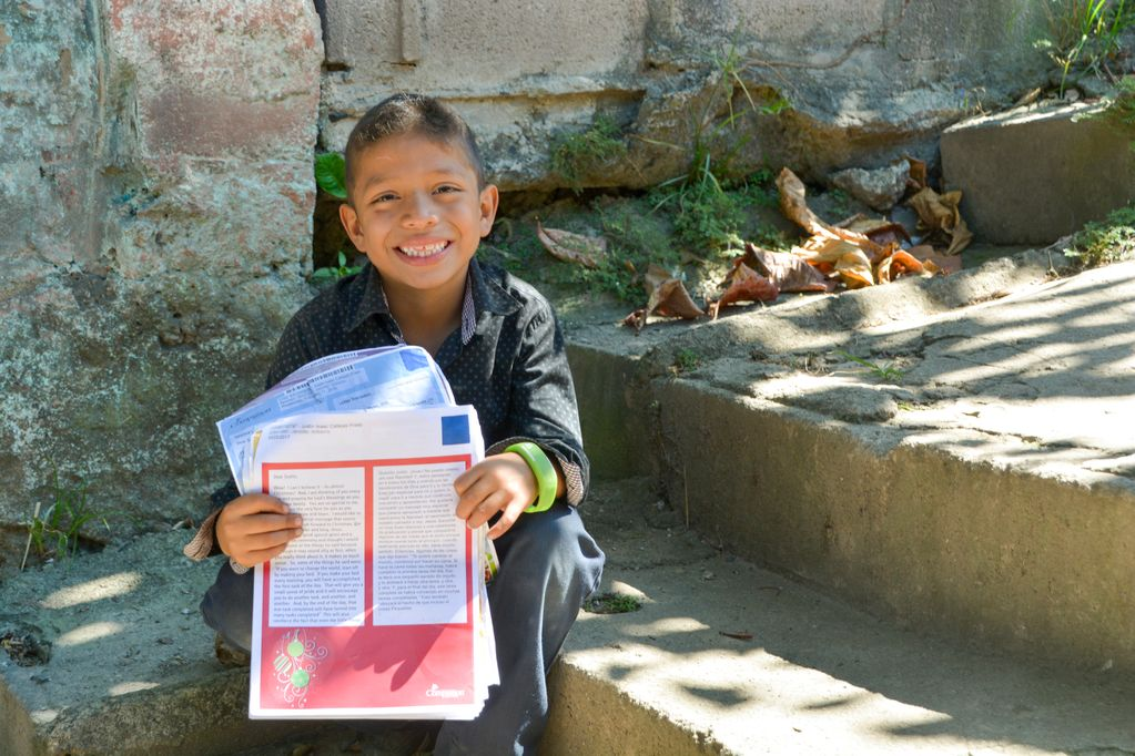 Justin, in El Salvador, proudly shows off a stack of letters from his sponsor.