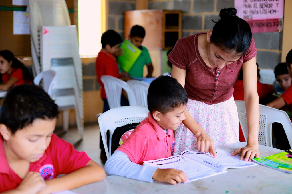 Débora, a tutor at a child development centre in Honduras, assists a child in writing a letter to his sponsor.