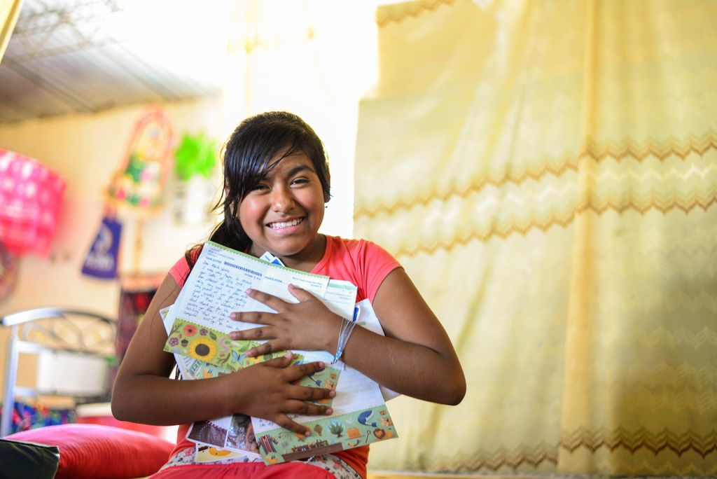 Maria sits in her home in Peru, clutching an armful of beloved letters from her sponsor.