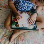 Sienna sits in her bedroom, drawing a picture to accompany a letter to her Compassion child, Praise.