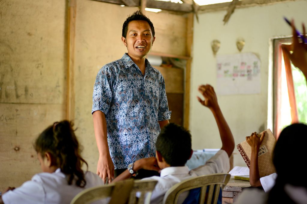 A man stands in a classroom made from plywood wearing a blue shirt, in front of children sitting in chairs raising their hands