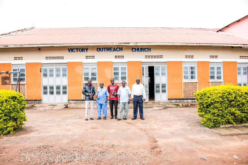 Five men in front of Victory Outreach Church