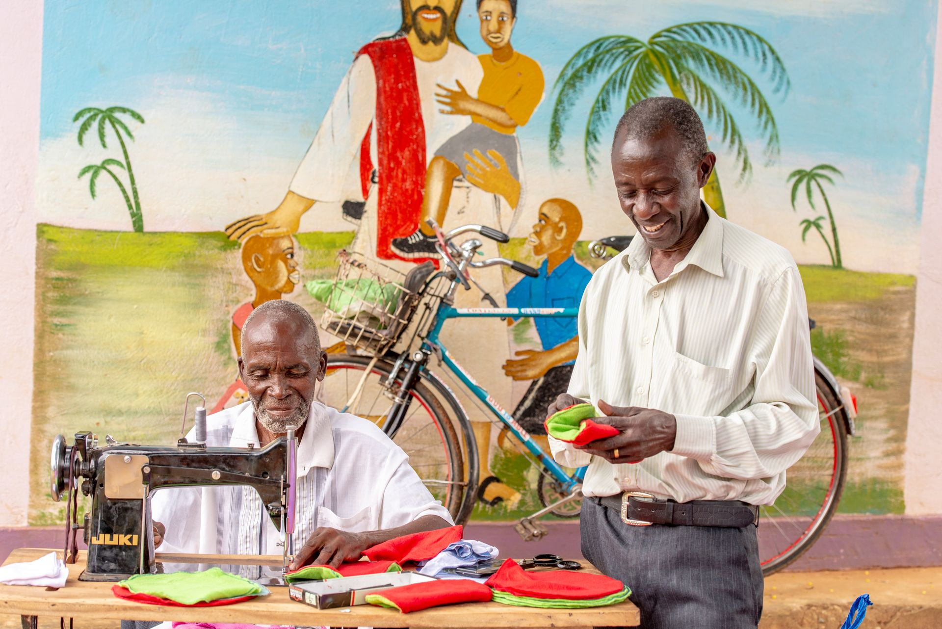 Two men at a table sewing sanitary pads.