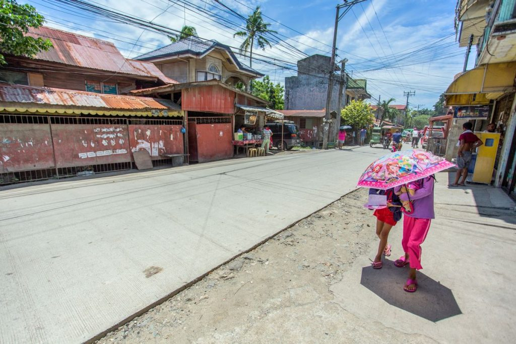 Two girls walk down the street with a pink umbrella covering their faces.