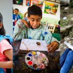 A collage of three kids featured in this post. On the left is Alondra, holding a tennis racquet and carrying a blue backpack. In the middle is Hector, wearing a green paint smock and working on a painting. On the right is Nazareth, who sits with her back against a tree with an open notebook on her lap.