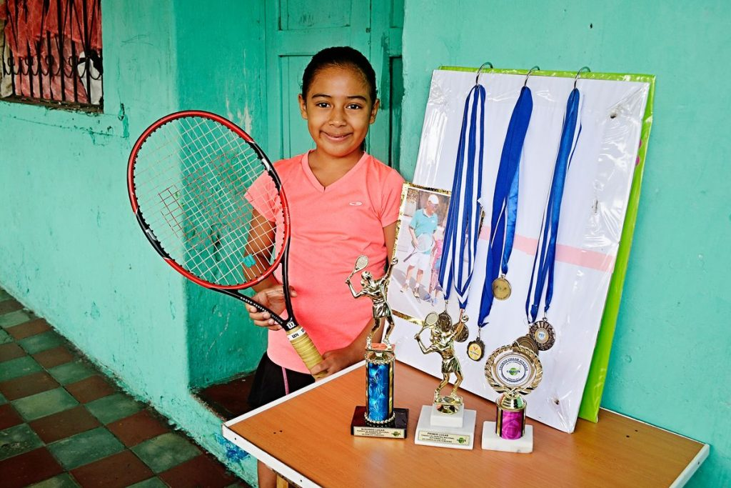 Alondra, wearing a pink shirt and holding her tennis racquet, smiles and poses with her medals and trophies.