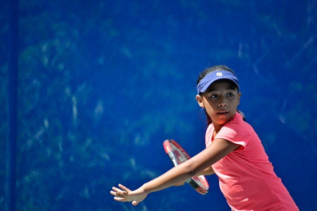 Alondra, wearing a pink shirt and blue visor, winds up with her tennis racquet to hit a ball.