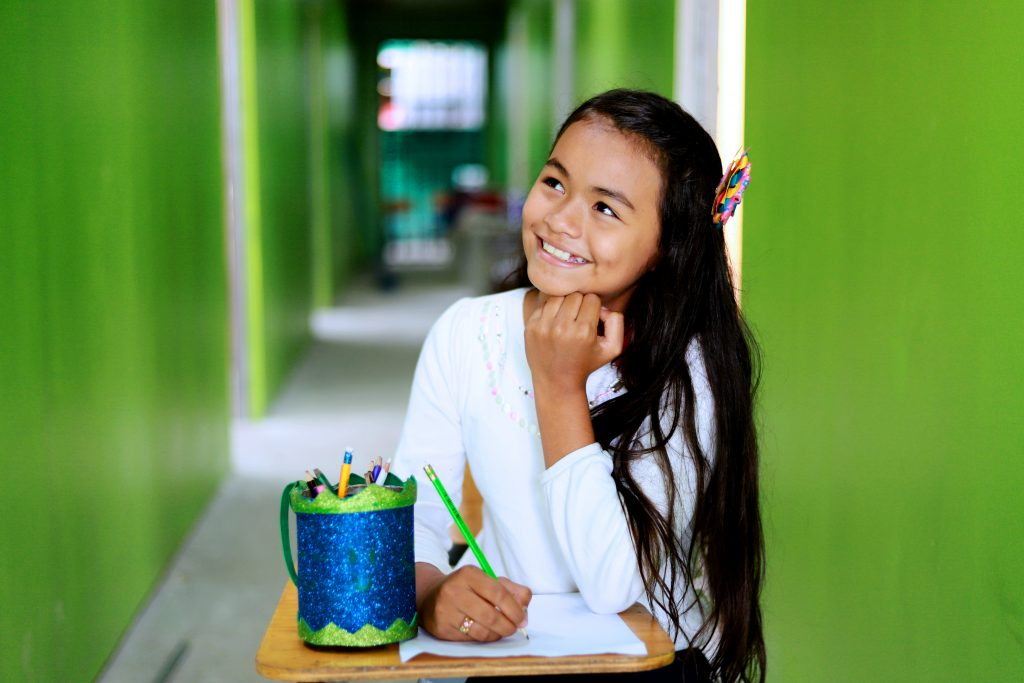 A young girl, Nazareth, sits at a desk with her chin on her first, looking up as she thinks. She is holding a green pencil.