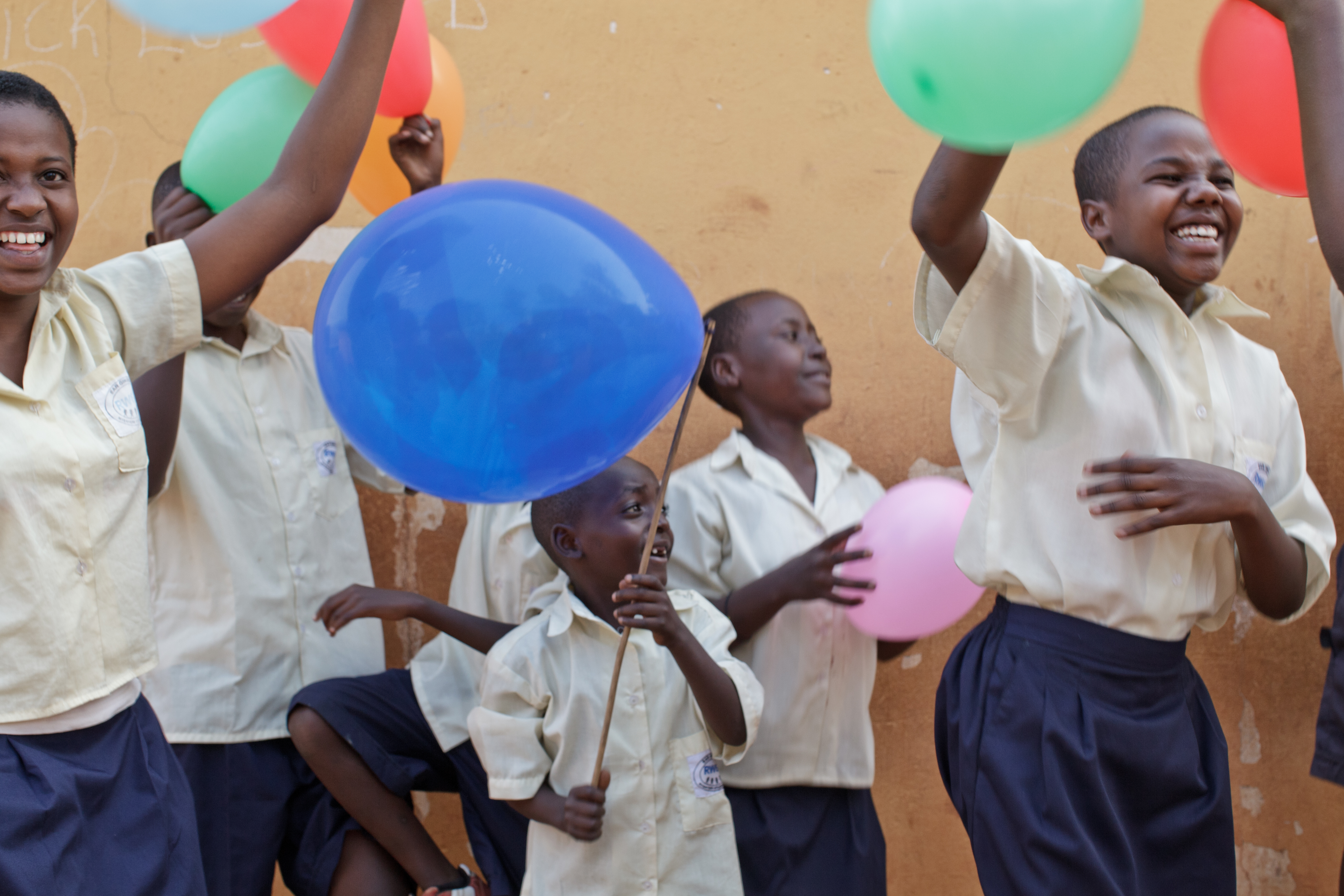 A group of children plays with multicolour balloons in Rwanda.