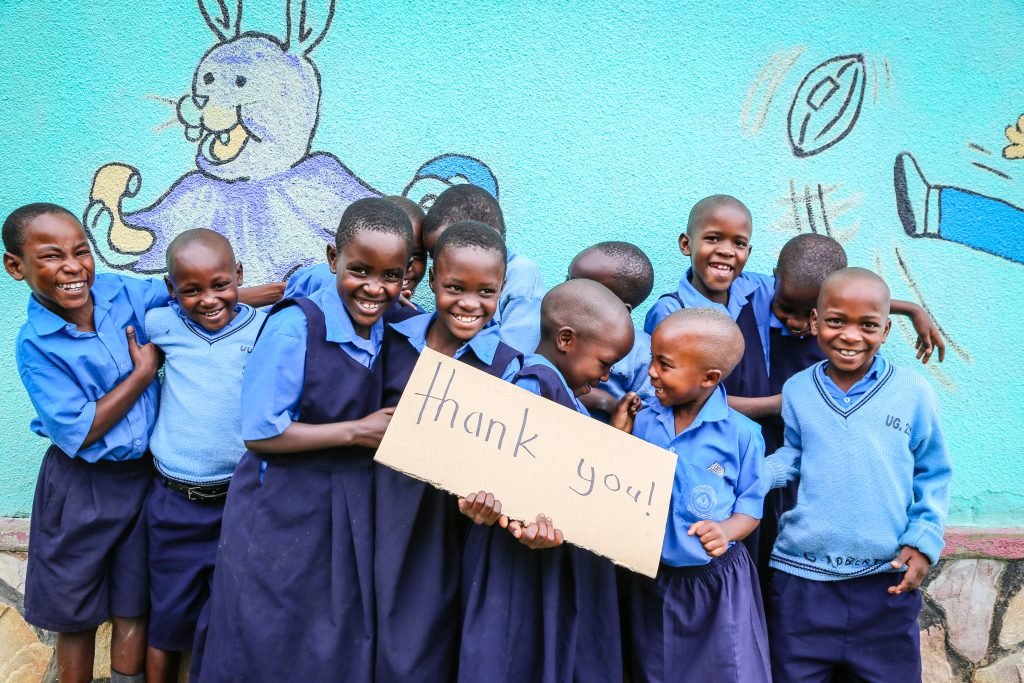 A group of Ugandan children in school uniforms hold a cardboard sign that says 'thank you'.