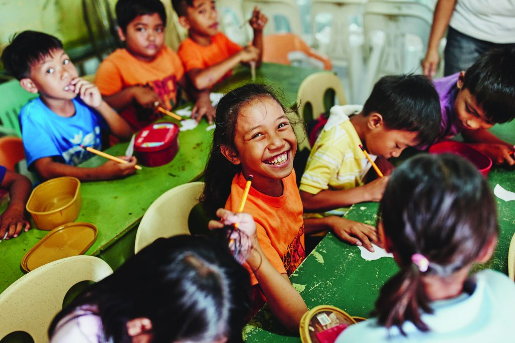A Filipino girl looks up from sitting at a table, smiling and wearing an orange teenager. Other engaged children surround her.