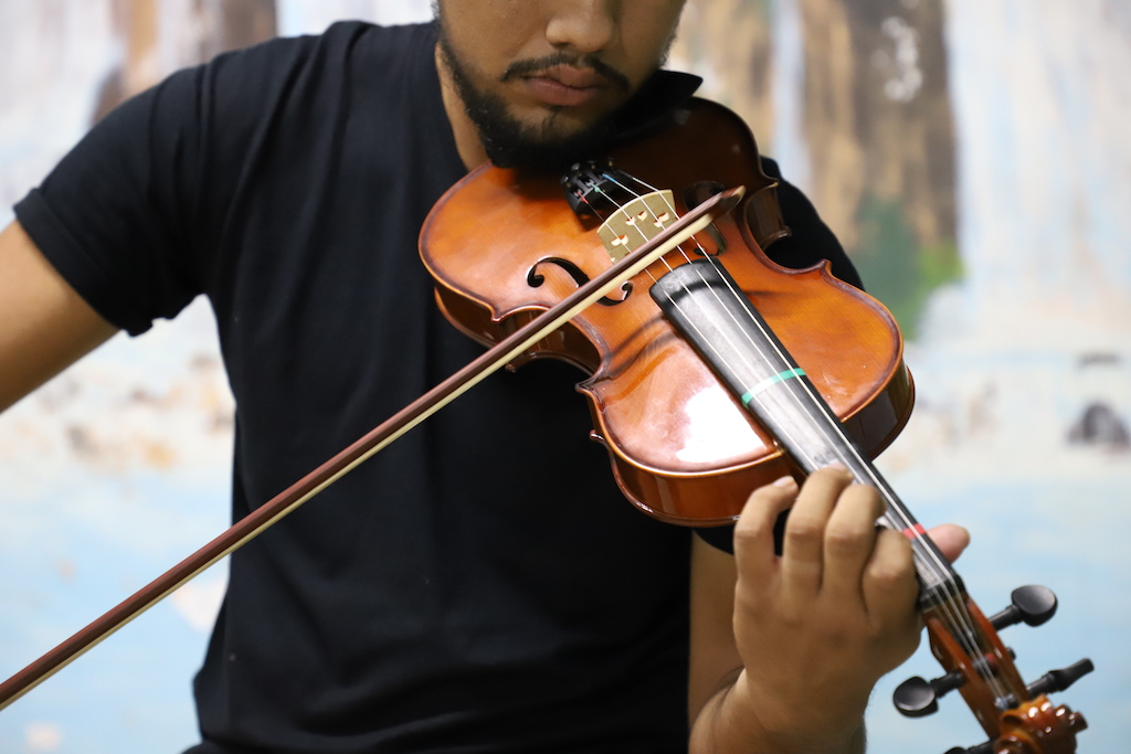 A man wearing a black t shirt is playing the violin. It is a closeup, without showing his eyes.