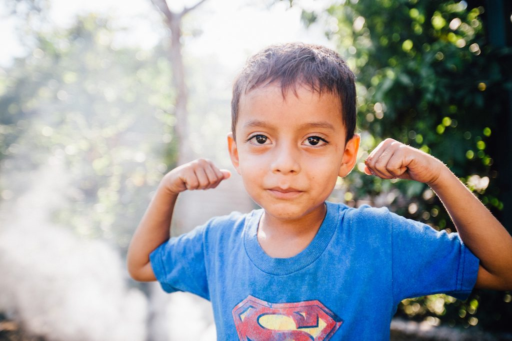 A young boy in a blue t-shirt stands flexing his arms.