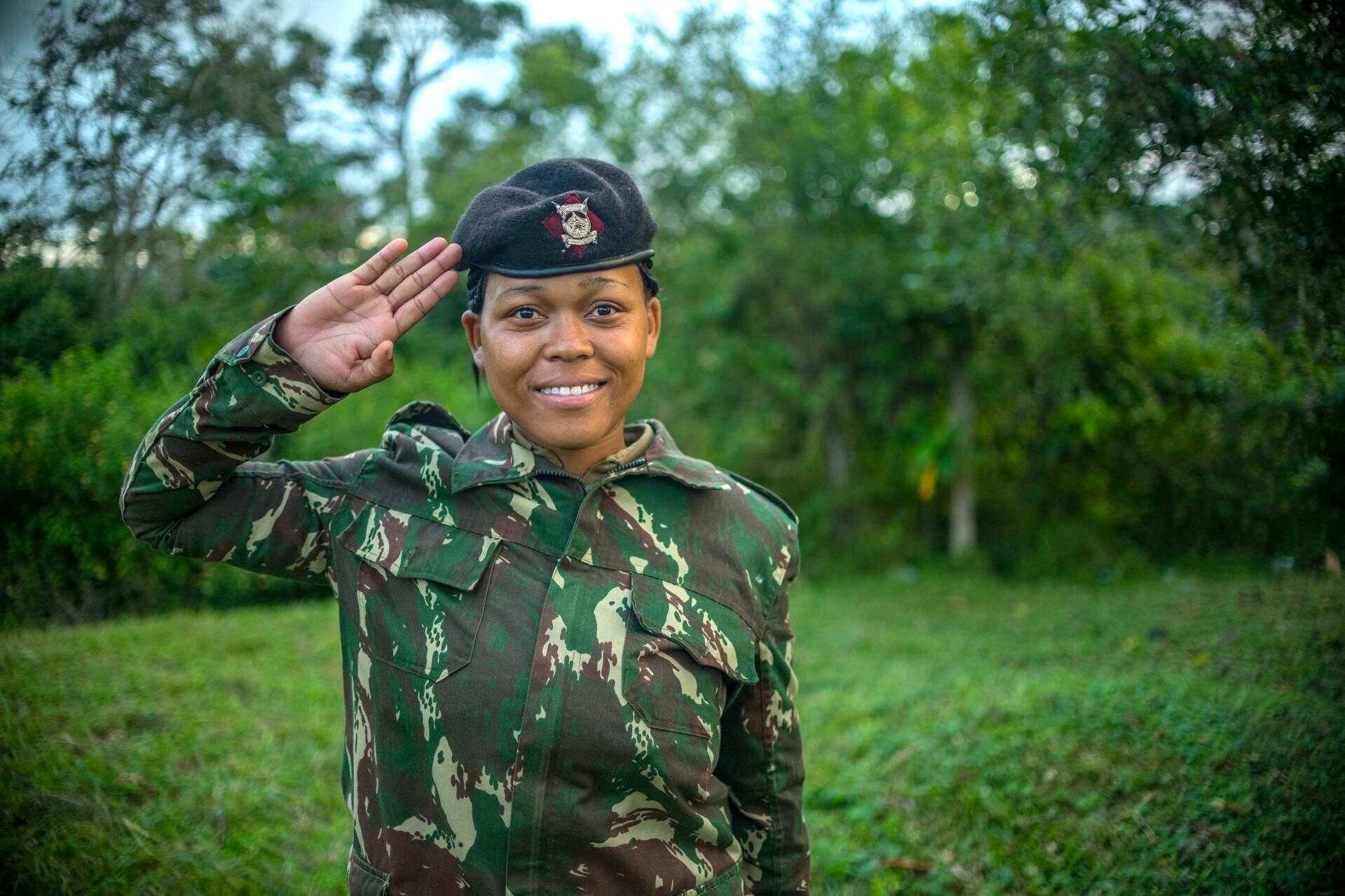 Miriam is pictured here in her uniform - a camoflauge top and green pants. She is wearing a hat. She is smilimg at the camera and saluting, and there are trees in the background.