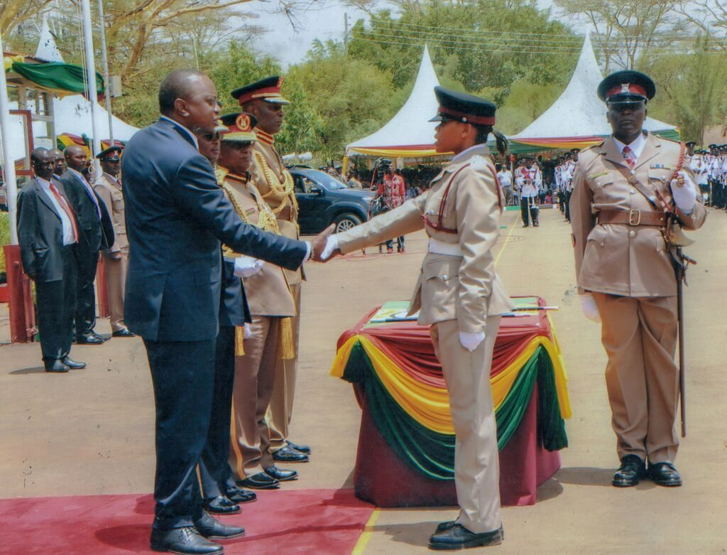 Miriam shakes the hand of the Kenyan president as she receives an award for being the fastest cadet to complete the quick march routine. She is wearing a dress uniform, tan pants and shirt, and black hat. There is a table with red, yellow and green tablecloths behind her.