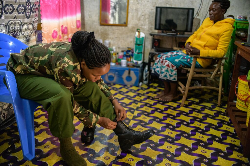 Miriam wearing a camoflauge shirt and green pants. She is sitting in the same room as her mother, who is wearing a yellow sweatshirt. Miriam is lacing up her boots.
