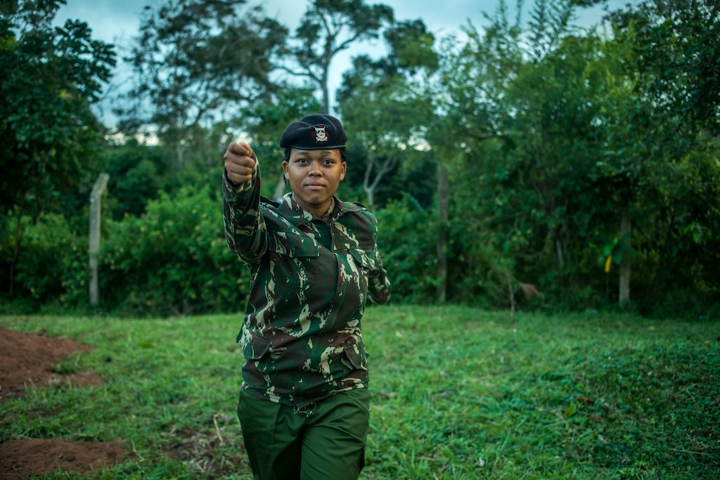 Miriam is standing in a field in front of trees. She is wearing a camoflauge shirt and a black hat. Miriam is looking at the camera and has her arm outstretched.