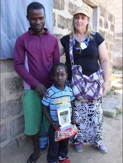 A woman stands with a boy and his father in front of their home.