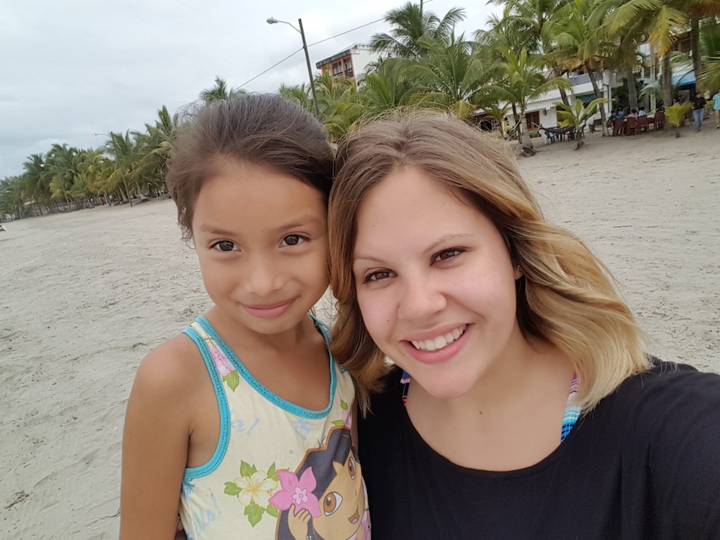A woman and a girl pose together on a beach.