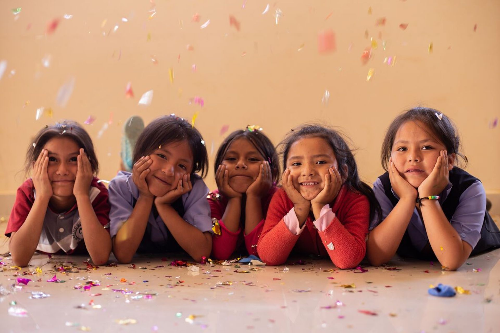 A row of girls lie on their stomachs with their chins in their hands, smiling, with confetti falling around them.