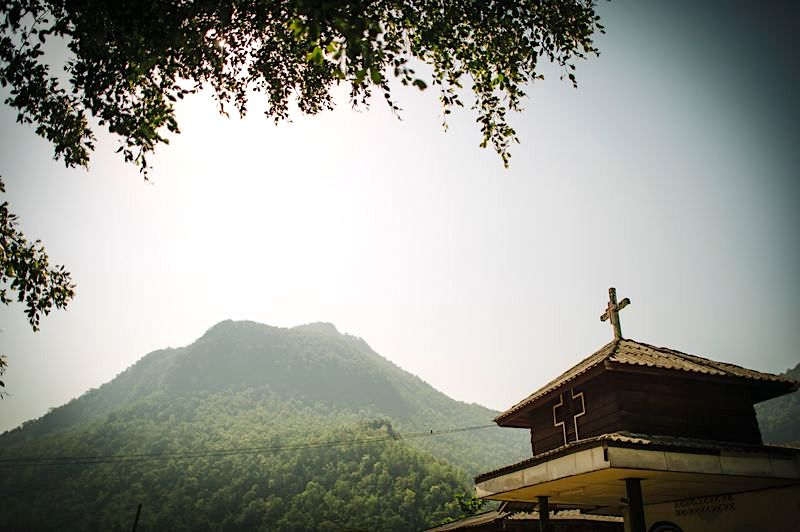 A church building with a mountain behind it.