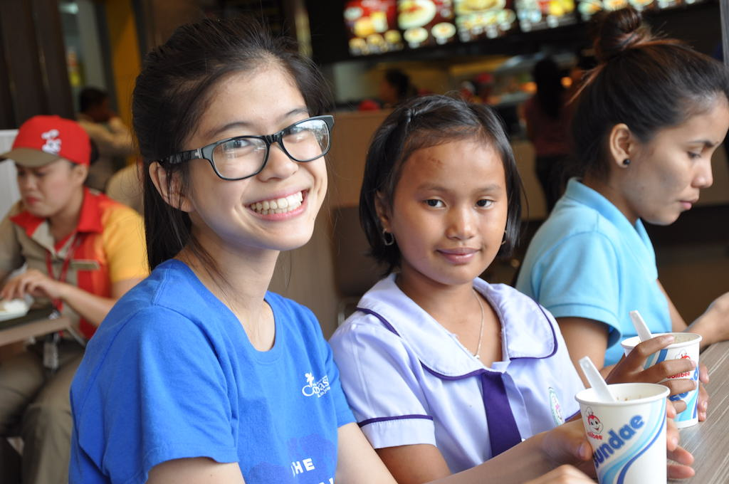 A young woman in a blue t-shirt sits next two a young girl in a purple school uniform. They are both looking at the camera.