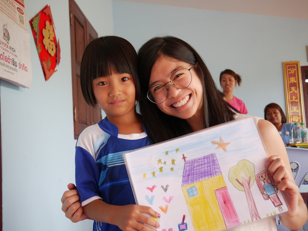 A young woman and a young girl stand together, holding up a child's drawing. Both are looking at the camera, smiling.