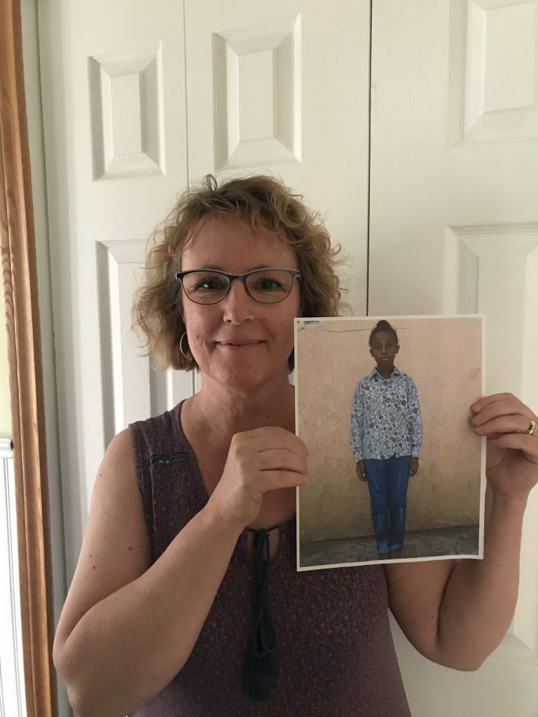 Karen holds a printed off photo of her sponsored child